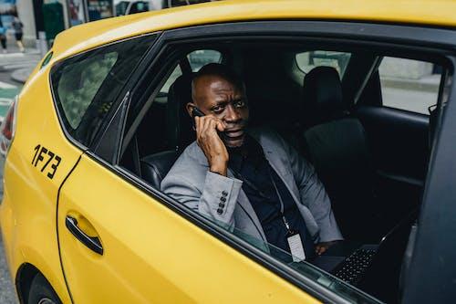 Ponderando Um Empresário Negro Andando De Táxi E Falando No Smartphone