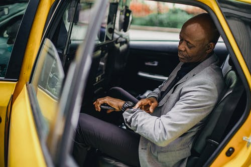Serious black businessman checking time on wristwatch in taxi