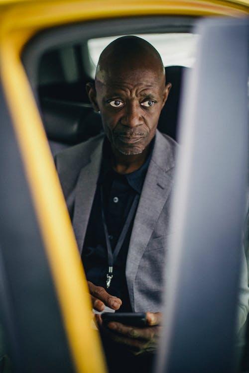 Pondering black businessman using smartphone in car