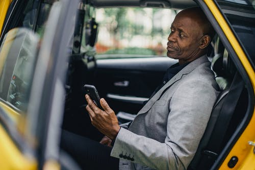 Contemplative black businessman using smartphone in taxi