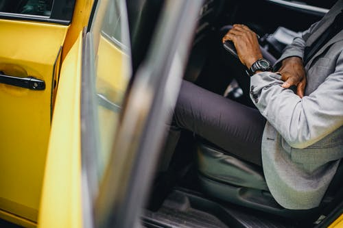 Side view of crop anonymous African American male in elegant suit checking wristwatch in car