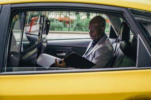 車の中で重要なレポートを調べる物思いにふける黒人起業家