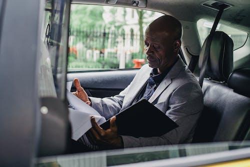 Orang Kulit Hitam Yang Bertanggung Jawab Yang Bekerja Dengan Kertas Di Dalam Mobil