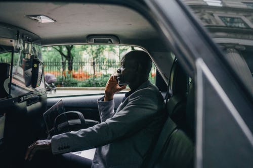 Black businessman talking on smartphone in car