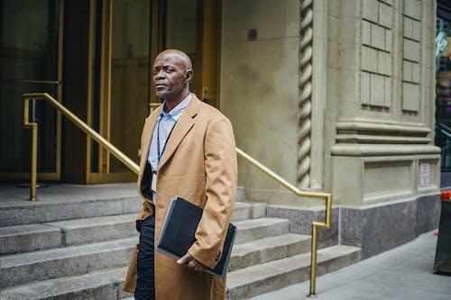 階段のある建物の近くにフォルダーを持つ深刻な黒人起業家