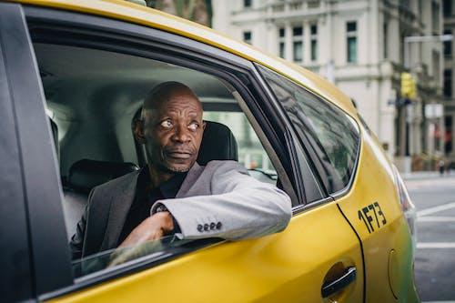 Black man in elegant coat in taxi