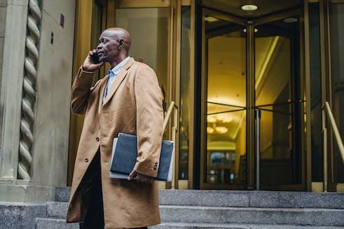 Schwarzer Geschäftsmann, Der Auf Smartphone Nahe Gebäude Spricht