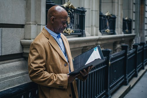 Experienced black lawyer reading documents on street