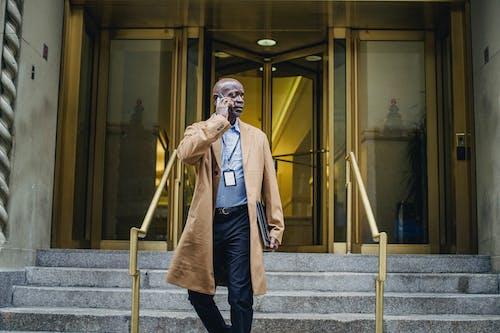 Pensive black man talking on phone walking down stairs