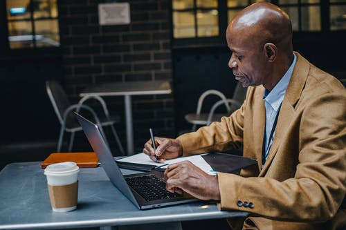 Side view of focused African American freelancer sitting at table with laptop and making notes on paper in cafe
