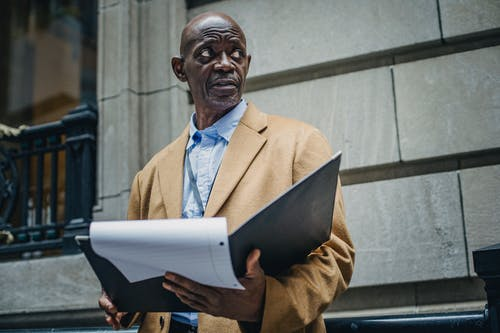 Low angle of gloomy African American man in trendy outfit standing with folder with documents in hands and looking away in daytime