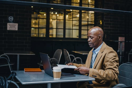 Thoughtful black man browsing laptop and opening documents in cafe