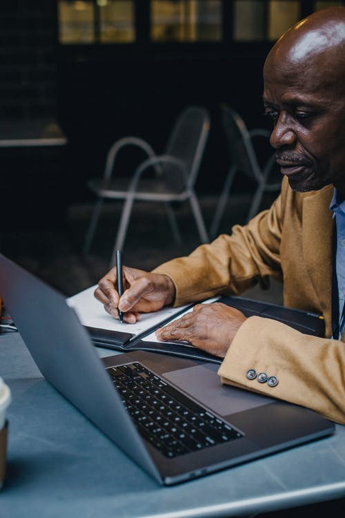 Focused African American man working on laptop in cafe