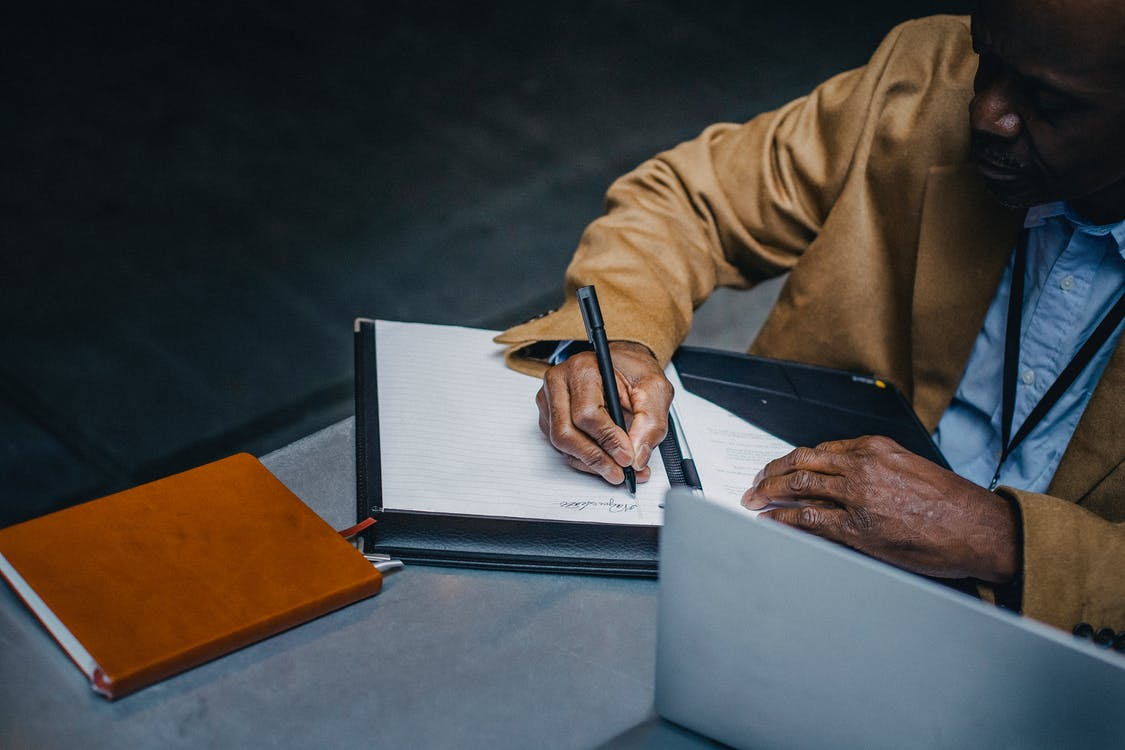From above of crop black executive in suit writing on paper near laptop and diary while working at desk