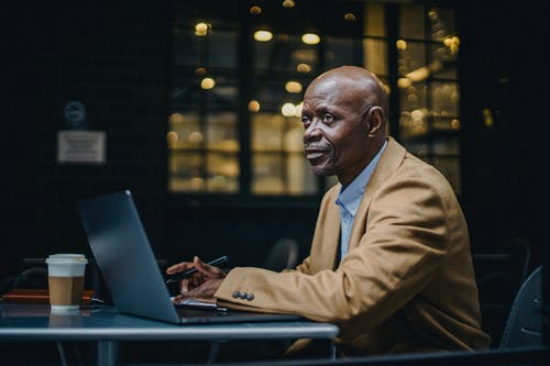 Black businessman with laptop and takeaway coffee in cafe