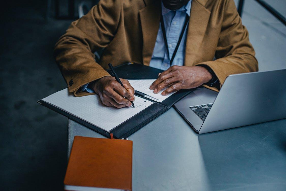 Cultivo Ejecutivo Masculino Negro Escribiendo En La Hoja De Papel Cerca De La Computadora Portátil
