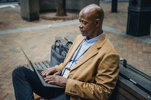 集中在镇上的笔记本电脑上打字的黑人商人