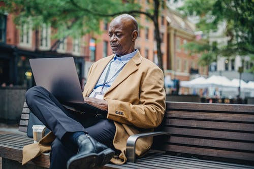 Serious African American executive watching laptop on bench in town