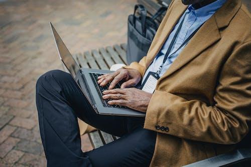 作物在街头长椅上的笔记本电脑上打字的黑人商人