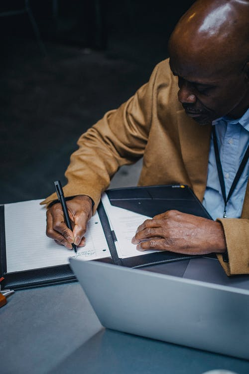 Crop focused African American male sitting at table with laptop and writing notes in planner