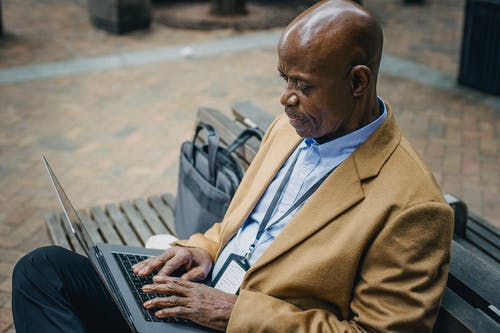 Crop black businessman sitting on bench and using laptop