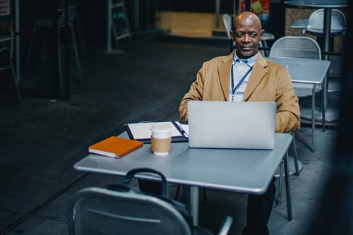 Empresario Negro Positivo Usando Laptop En Café Al Aire Libre