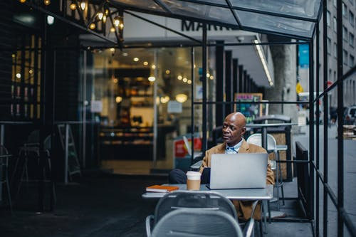 Focused black businessman with laptop sitting in outdoor cafeteria