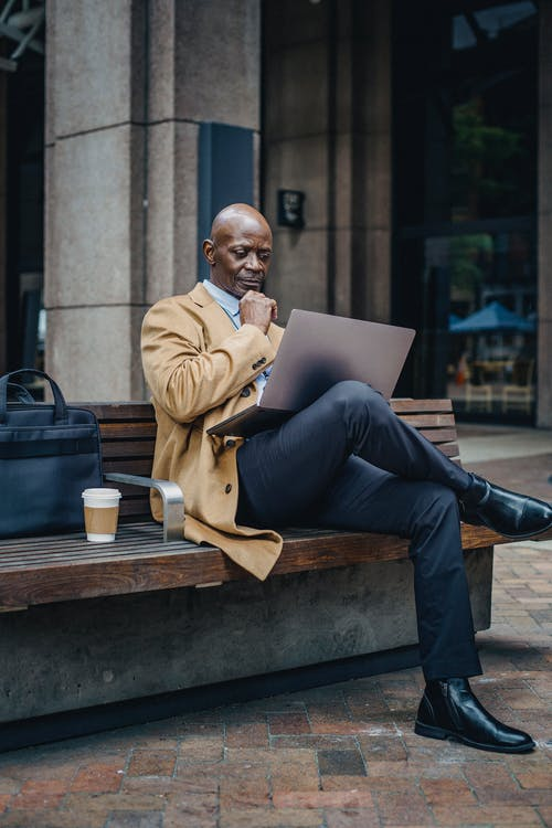 Pensive adult African American businessman wearing stylish formal clothes sitting on street bench and browsing netbook on laps while touching chin in thoughts