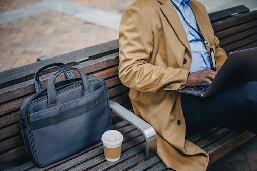 Crop faceless black man using laptop on street bench