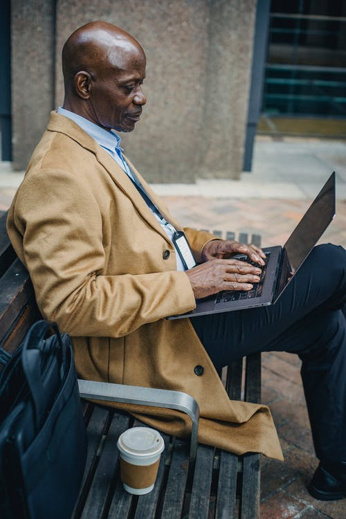 Side view thoughtful African American businessman in trendy formal suit sitting on street bench and typing on netbook on laps