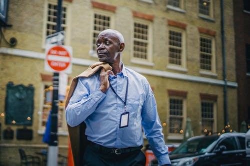 Serious black man crossing road on busy street