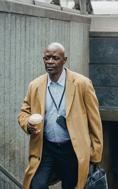 Homme D'affaires Noir Contemplatif Debout Avec Du Café à Emporter Près De L'entrée Du Métro