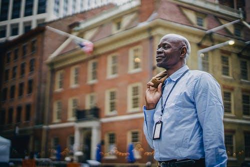 Positive black businessman standing on urban city street