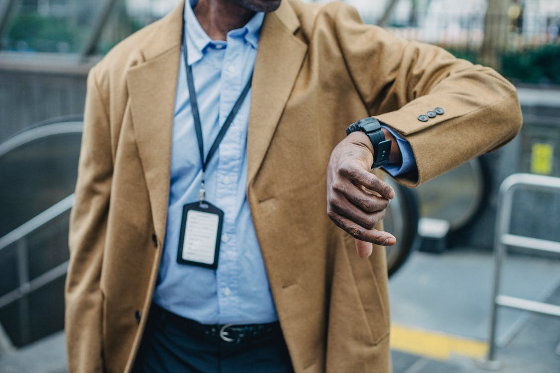 Crop anonymous African American businessman in elegant formal suit looking at wristwatch while standing near metro entrance