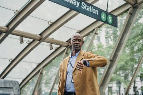 Pondering black businessman checking time on wristwatch near subway station