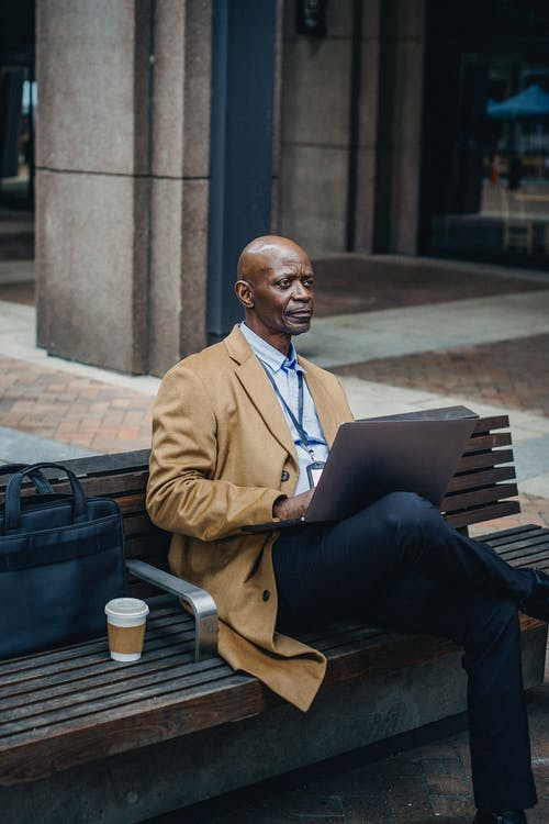 Concentrated African American businessman wearing formal clothes sitting on street bench with legs crossed and browsing modern netbook while looking away in thoughts