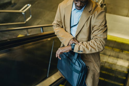 From above crop punctual African American businessman riding escalator and checking time on wristwatch while leaving metro station