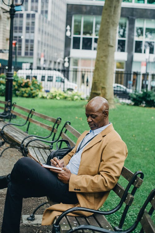Side view concentrated adult African American businessman wearing trendy formal clothes sitting on park bench with legs crossed and taking notes in diary