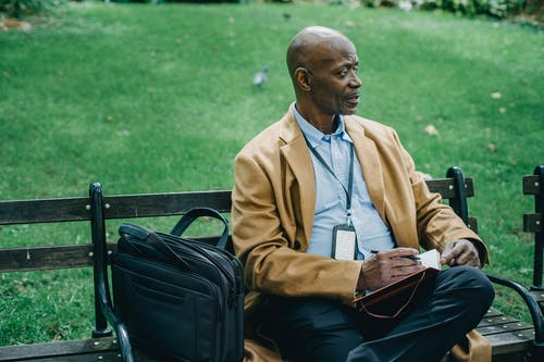 Thoughtful African American businessman in formal outfit sitting on wooden bench in park and writing in notebook while looking away pensively