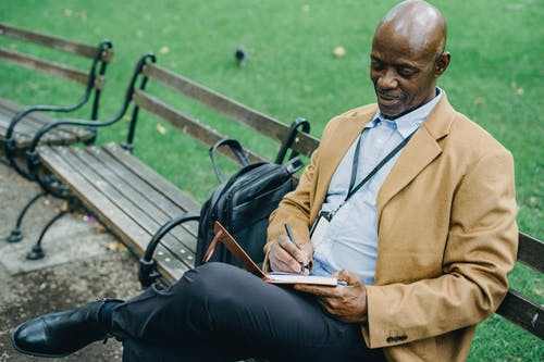 Positive black man writing in notebook in park