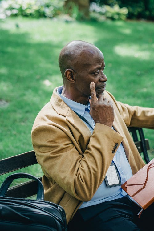 Pondering mature African American male executive with agenda and badge touching cheek while looking away in town