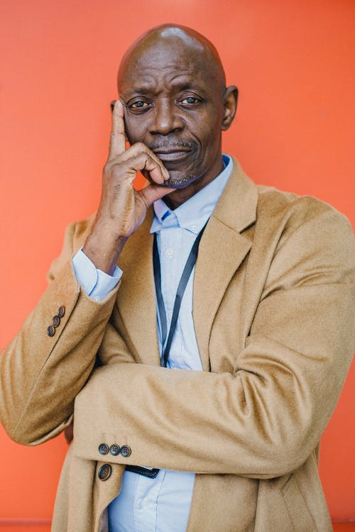 Confident African American businessman touching chin on orange background