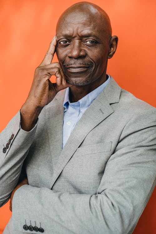 Intelligent black businessman in suit on orange background