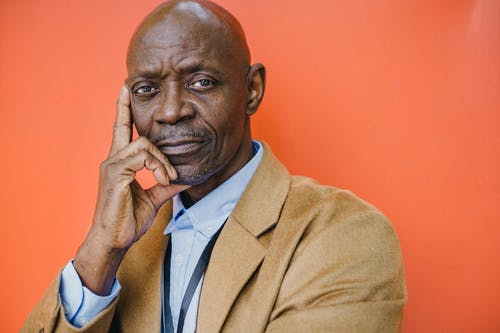 Confident middle aged bald African American male in elegant suit looking at camera with hand on cheek against orange background