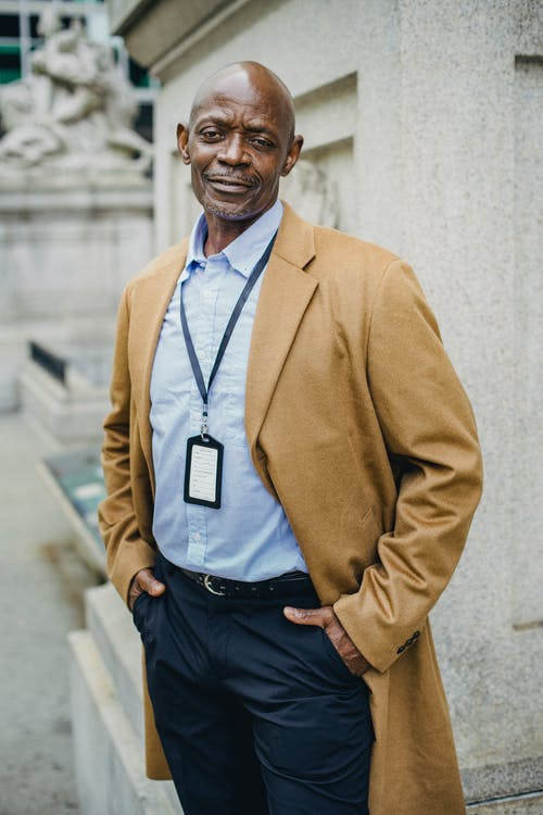 Self assured mature African American male manager in formal clothes and coat standing on street with hands in pockets and looking at camera