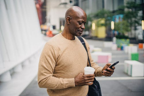 Confident middle aged African American man in stylish outfit standing on city street with takeaway coffee in hand and messaging on mobile phone