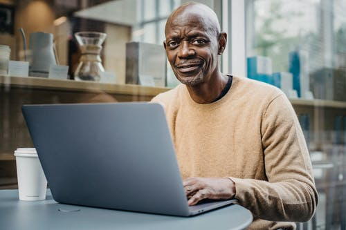 Positive mature bald African American male freelancer smiling and looking at camera while working on laptop sitting in cafe with cup of takeaway coffee