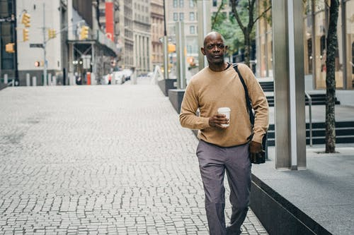 Self assured mature black male entrepreneur in stylish clothes walking on city street with cup of takeaway coffee and laptop bag during break