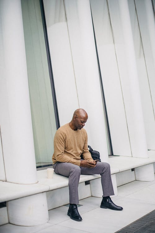 Serious black guy resting on city bench and using smartphone