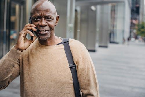 Bald black man talking on smartphone on street